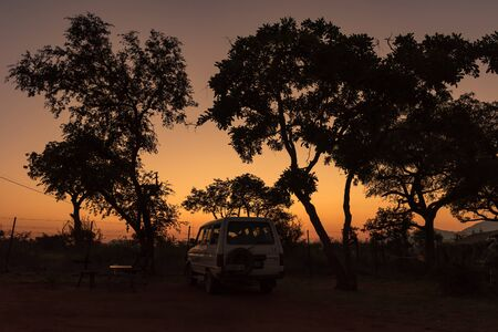 KRUGER NATIONAL PARK, SOUTH AFRICA - MAY 4, 2019: Sunrise at a camping site in the Malelane Bush Camp in the Kruger National Park. A vehicle is visible