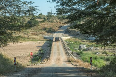 KRUGER NATIONAL PARK, SOUTH AFRICA - MAY 4, 2019: Single lane low water road bridge on road S25 over the Bume River. A vehicle is crossing the river
