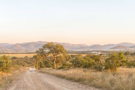 KRUGER NATIONAL PARK, SOUTH AFRICA - MAY 3, 2019: The road to the Malelane Bush Camp in the Kruger National Park. A vehicle and Malelane town are visible