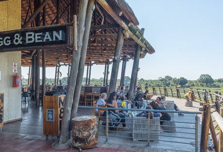 KRUGER NATIONAL PARK, SOUTH AFRICA - MAY 4, 2019: A restaurant with viewing deck in the Lower Sabie Rest Camp in the Kruger National Park. People are visible
