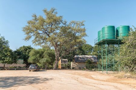 KRUGER NATIONAL PARK, SOUTH AFRICA - MAY 4, 2019: A view of the Nkuhlu Picnic Site in the Kruger National Park. A vehicle and water tanks are visible
