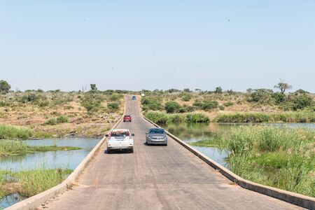 KRUGER NATIONAL PARK, SOUTH AFRICA - MAY 4, 2019: The low level bridge over the Sabie River near Lower Sabie in the Kruger National Park. Vehicles are visible
