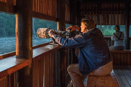 KRUGER NATIONAL PARK, SOUTH AFRICA - MAY 6, 2019: Inside the hide at Lake Panic near Skukuza. People and a camera with long lens are visible