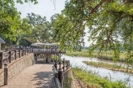 KRUGER NATIONAL PARK, SOUTH AFRICA - MAY 5, 2019: The waterfront at Skukuza Restcamp. The Sabie River and a restaurant are visible Redakční