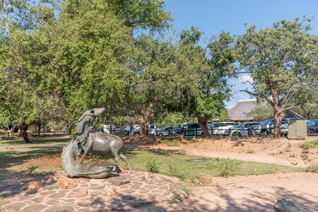 KRUGER NATIONAL PARK, SOUTH AFRICA - MAY 5, 2019: A scene in the Skukuza Restcamp. People, vehicles and a statue of two kudu bulls fighting are visible