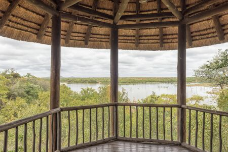 KRUGER NATIONAL PARK, SOUTH AFRICA - MAY 11, 2019: A shaded viewing deck in the Mopani Rest Camp of the Kruger National Park. The Pioneer Dam is visible Editorial