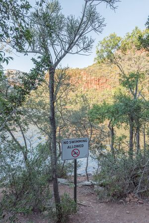A no swimming sign on the peninsula hiking trail in the Blyde River Canyon. The Blyderivierspoort Dam is visible
