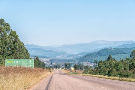A view of the landscape on road R532 near Sabie. A directional sign is visible