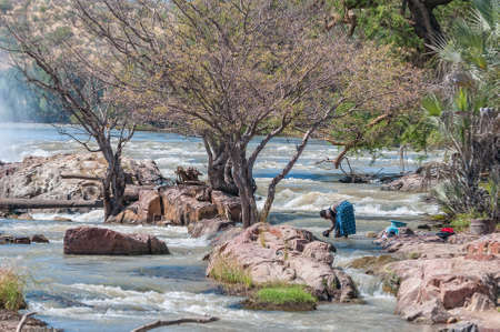 EPUPA, NAMIBIA - MAY 24, 2011: A woman washing clothes in the Kunene River at the top of the Epupa waterfalls