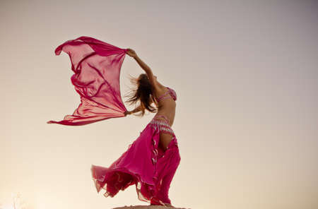 Ni�a bonita celebraci�n de tela de color rosa en el viento con el cielo de fondo photo