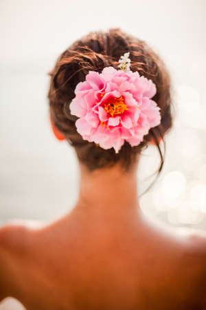 hair back: brunette woman with pinkroses in hair, vertical orientation Stock Photo