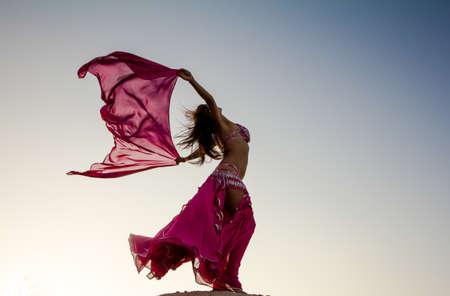 Menina bonita que prende um pano-de-rosa no vento com fundo do céu
