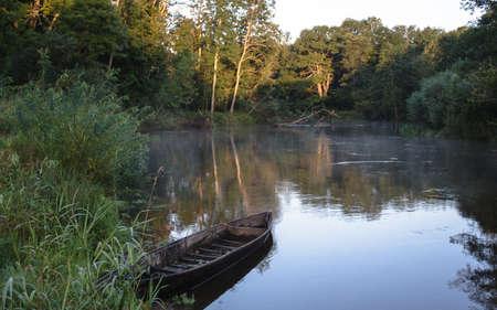 Rio bonito e barco a remos velho na grama verde Imagens