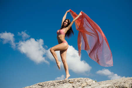 Pretty girl holding pink cloth in wind with sky background photo