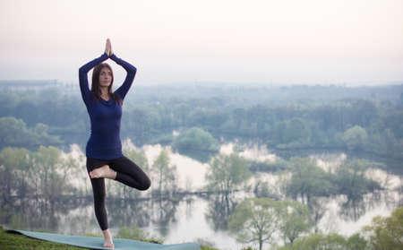 Mulher da ioga no parque fundo verde