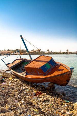 Barco vermelho deitado na praia