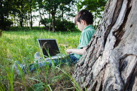 laptop outside: boy using his laptop outdoor in park on grass Stock Photo