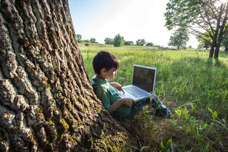 boy using his laptop outdoor in park on grass photo