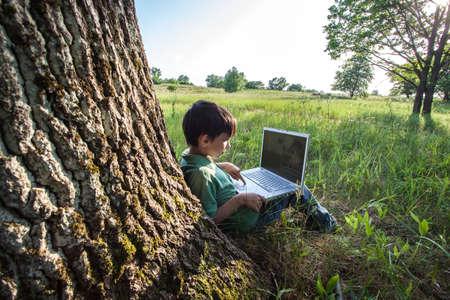 rapaz usando seu portátil ao ar livre no parque na grama