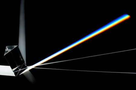Prism splitting white light into a spectrum on a black background