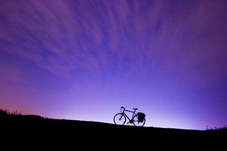 Silhouette d'une bicyclette sur une colline dans la nuit avec un grand ciel Banque d'images