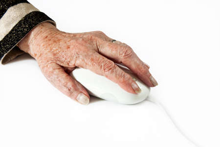 Elderly Hand on Computer Mouse on light plain background photo