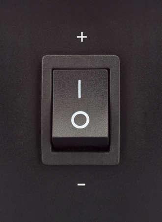 Black toggle switch on black surface - positive negative