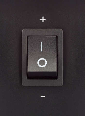 Black toggle switch on black surface - positive negative