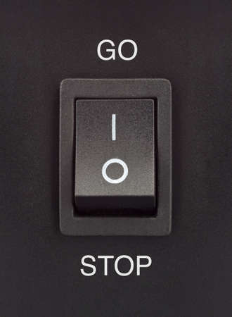 light switch: Black toggle switch on black surface - Go Stop Stock Photo