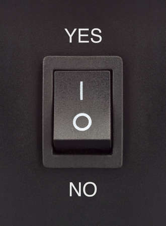 Black toggle switch on black surface - yes no