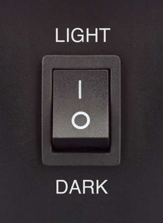 off: Black toggle switch on black surface - light dark