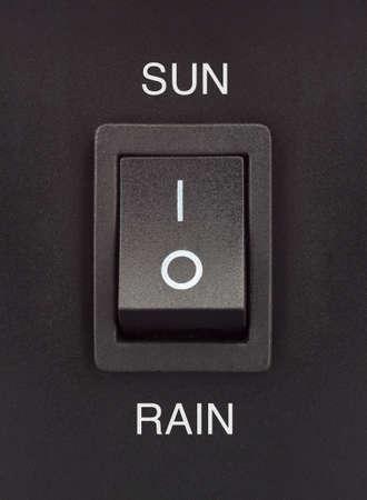 Soleil ou pluie interrupteur � bascule noir sur une surface noire positif n�gatif Banque d'images