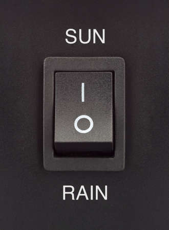 Sun or Rain black toggle switch on black surface positive negative Stock Photo - 16842328