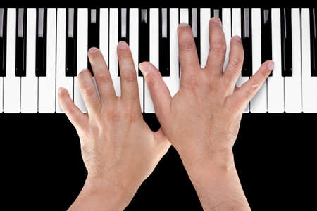 keyboard player: Hands playing a chord of Ab major over C bass on a piano keyboard shot from above with a black background.