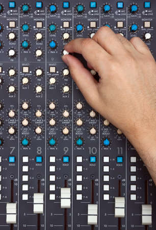 Hand turning knob on a mixing desk photo