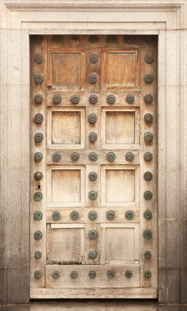 Old heavy wooden oak panel door in stone frame Stock Photo - 18305374