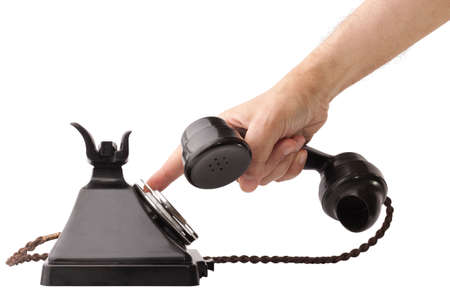 Hand holding the receiver and dialing an old bakelite telephone. GPO 200 Series. 232 model. Isolated on white with clipping path Stock Photo