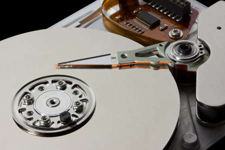 Open hard disk drive showing the read write arm and platter Stock Photo