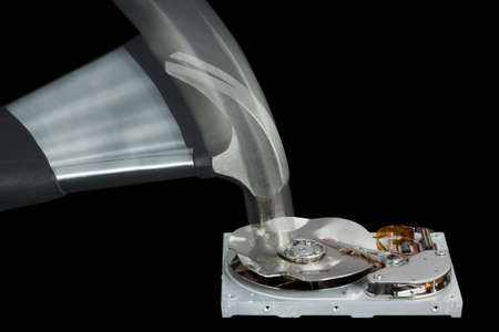 Open Hard Disk Drive Being Destroyed with a Hammer on a black background