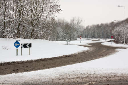 Roundabout and road in snowy conditions with road signs
