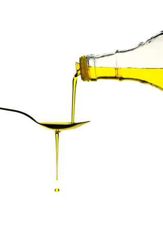 Extra virgin olive oil pouring over a spoon isolated on white with a clipping path Stock Photo