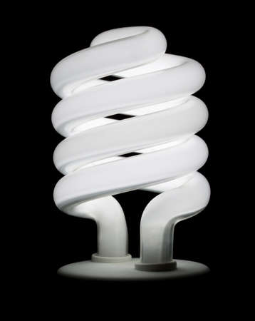 Compact fluorescent light bulb lit against a black background isolated