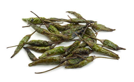 Dried green bird's eye chillies on a white background