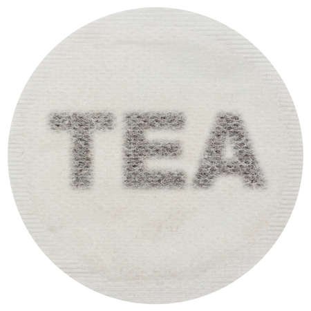 Tea bag with tea in the shape of the word TEA - Isolated on white
