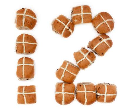 bollos: Docena de bollos cruzados calientes en la forma del número doce en el fondo blanco de Baker