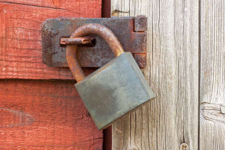Rusty padlock on wooden garden shed door