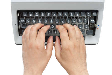 Hands on a typewriter keyboard shot from above isolated on white background with clipping path