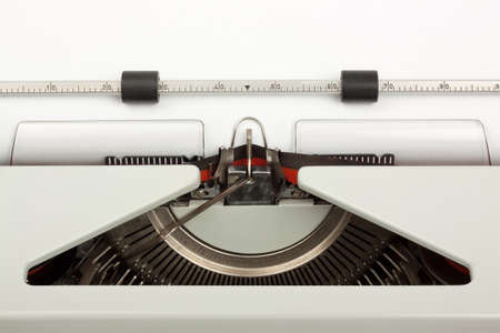 Close-up of typewriter with typebar striking ribbon; with blank sheet of paper. Space for copy.