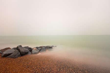 Rocks on a pebble beach plain overcast sky and long exposure Stock Photo