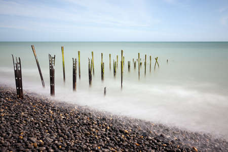Rusty Posts on Beach going out to see smooth water clear sky long exposure space for copy